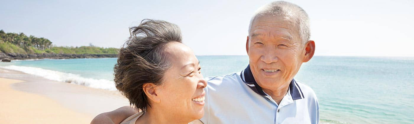 happy senior couple walks along the beach and reflects on health care costs in retirement