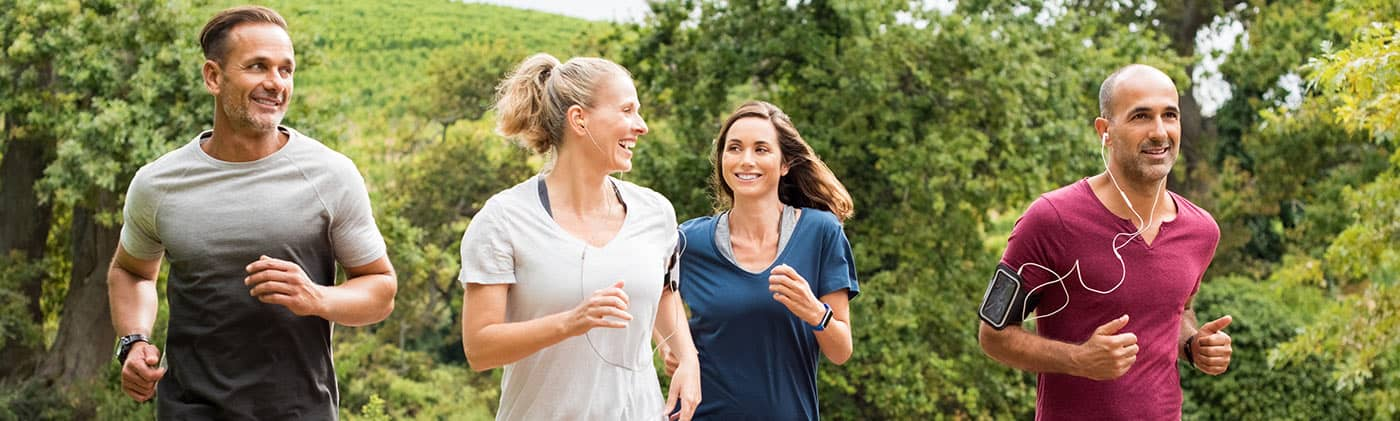middle-aged group of two male and two female joggers run together and discuss divorce and retirement