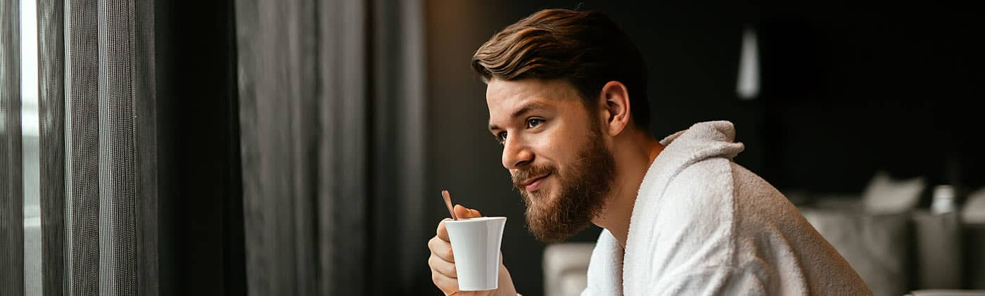 Man drinking coffee in a robe in his hotel room, enjoying a financial windfall during a vacation