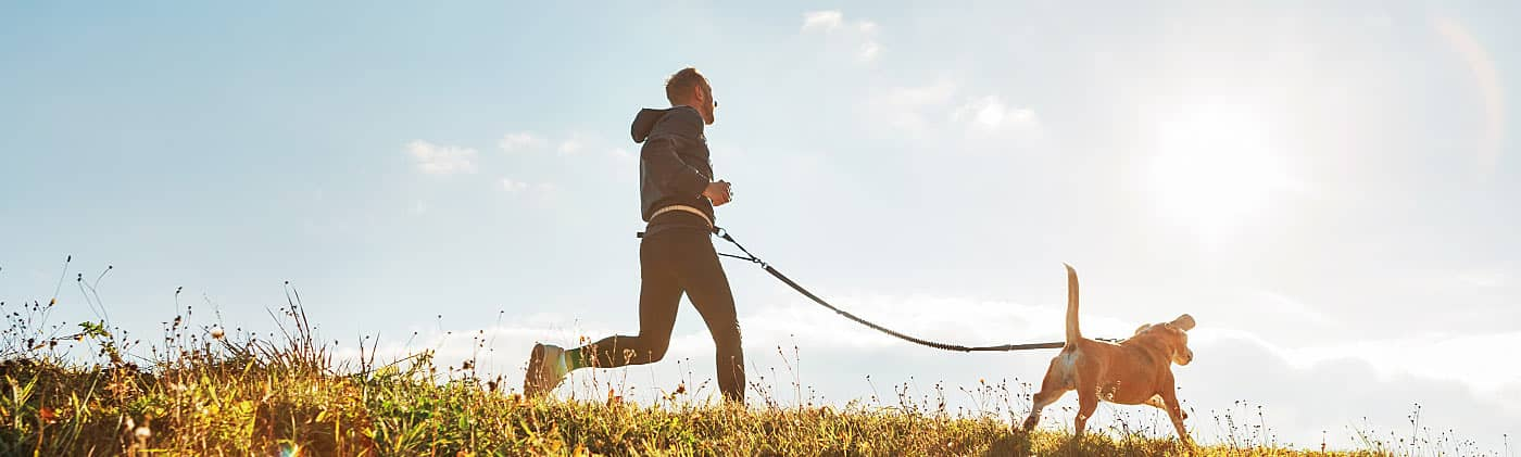 Man on a run with his dog on a sunny day after wondering what is an HSA