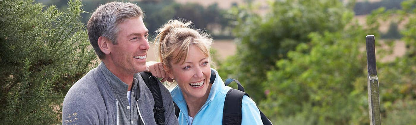 middle-aged couple checks map on hike as they consider buying convertible term life insurance