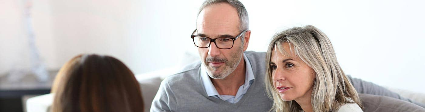 Mature couple meeting with financial advisor to discuss investments: investing after retirement