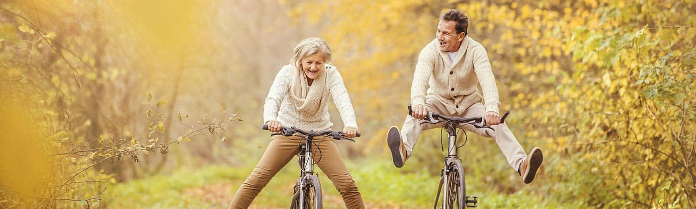 mature couple rides bikes in the woods and discusses choosing a single premium immediate annuity