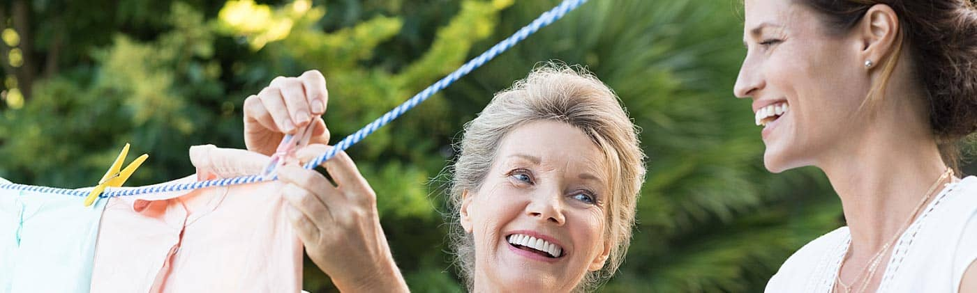 Mature mother hanging clothes outside with her daughter: benefits of whole life insurance