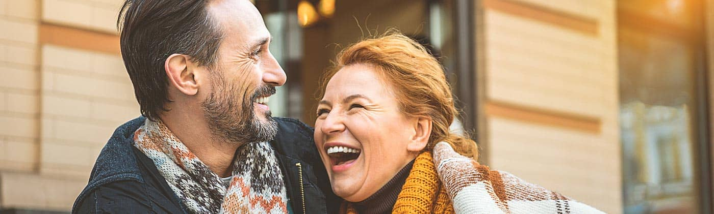 middle-aged couple laughs together outside of a café and discusses how to start planning for retirement