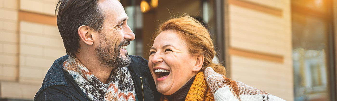 Middle-aged couple laughing in a cafe: planning for retirement