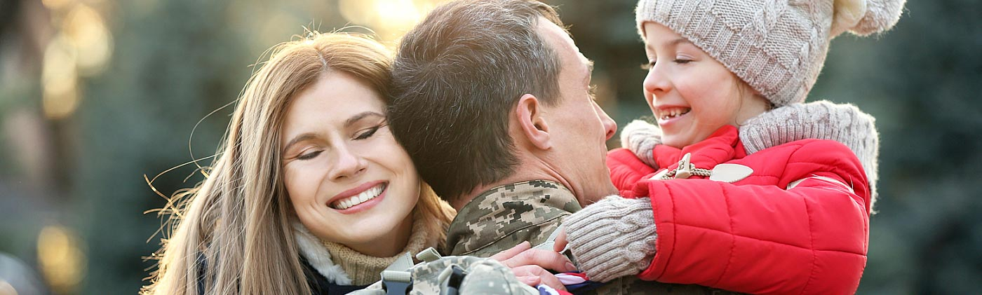 Military serviceman returning home and hugging his wife and child: life after the military