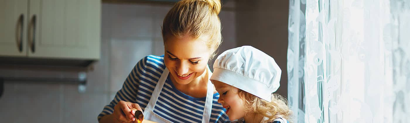 mom cooks with daughter after researching difference between accidental death insurance and life insurance