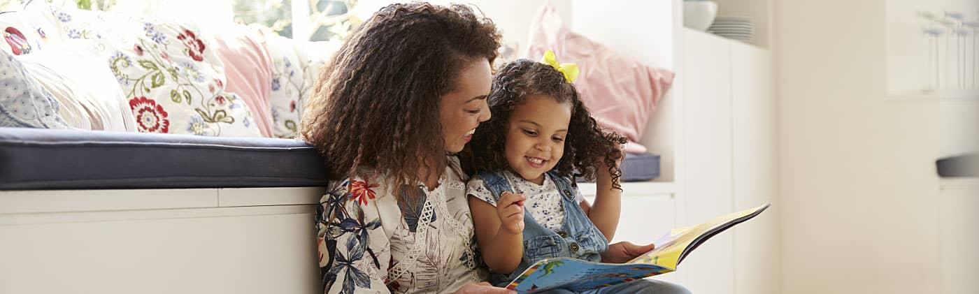 Mother reading with her daughter at home and thinking about how much does it cost to raise a kid
