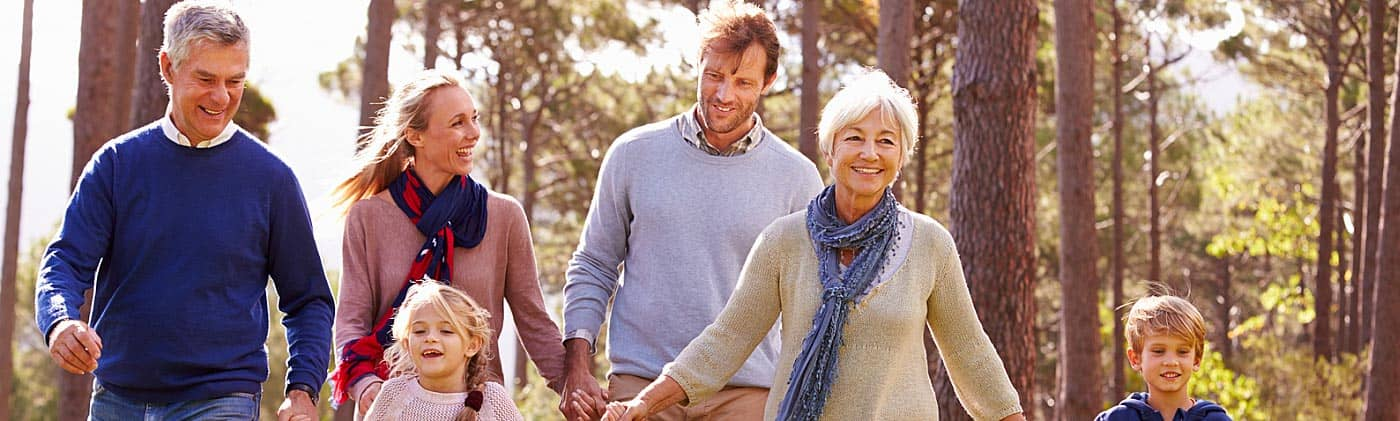 multigenerational family discusses avoiding common retirement mistakes on a fall walk in the woods