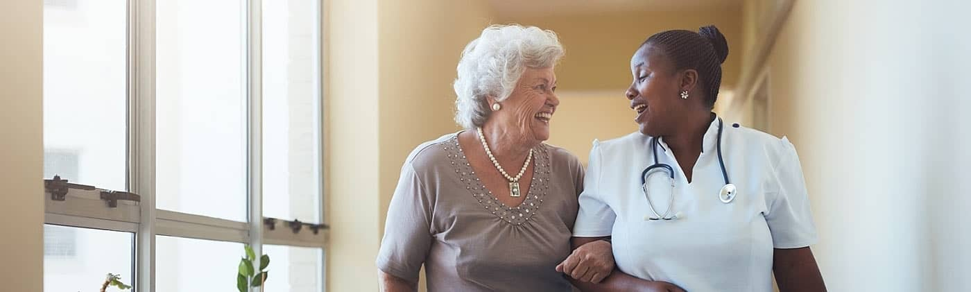 Nurse aiding a senior woman who uses the benefits of long-term care insurance to cover care fees
