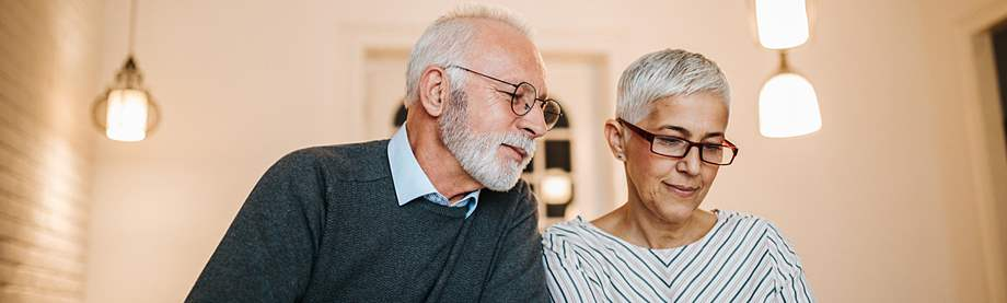 older couple doing paperwork and planning their retirement budget