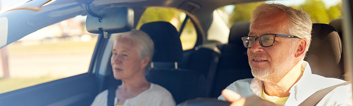 Older couple driving and discussing retirement expenses like transportation