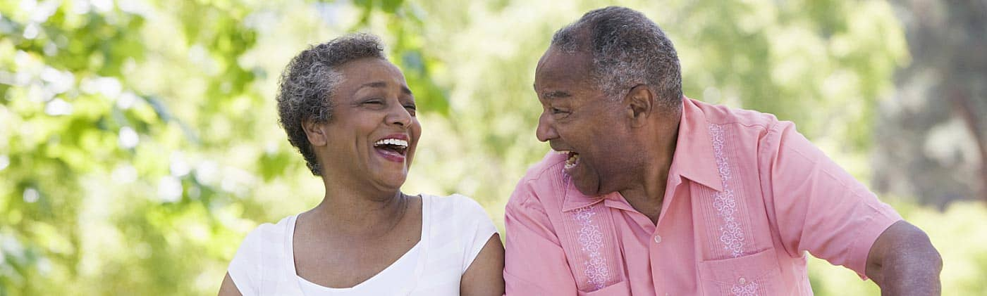 older couple laughs as they ride bikes down a path and discuss whole life insurance together