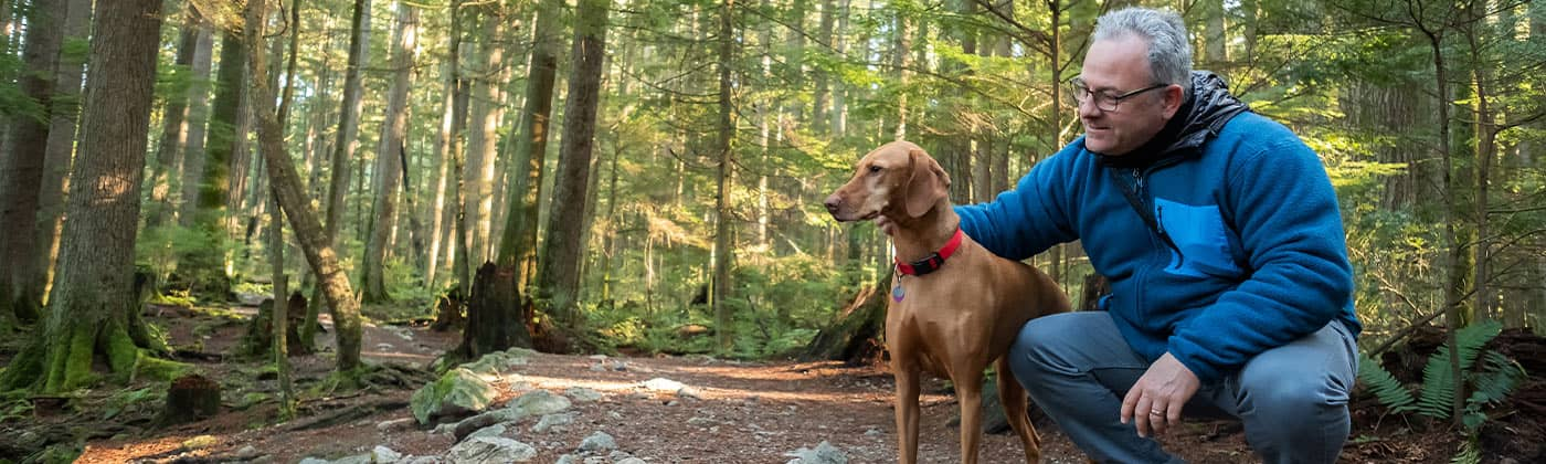 Older man walking with dog through woods thinking about finances as a widower