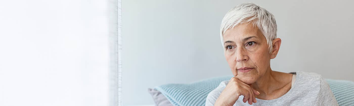 Older pensive woman looking out the window and thinking about running out of money in retirement