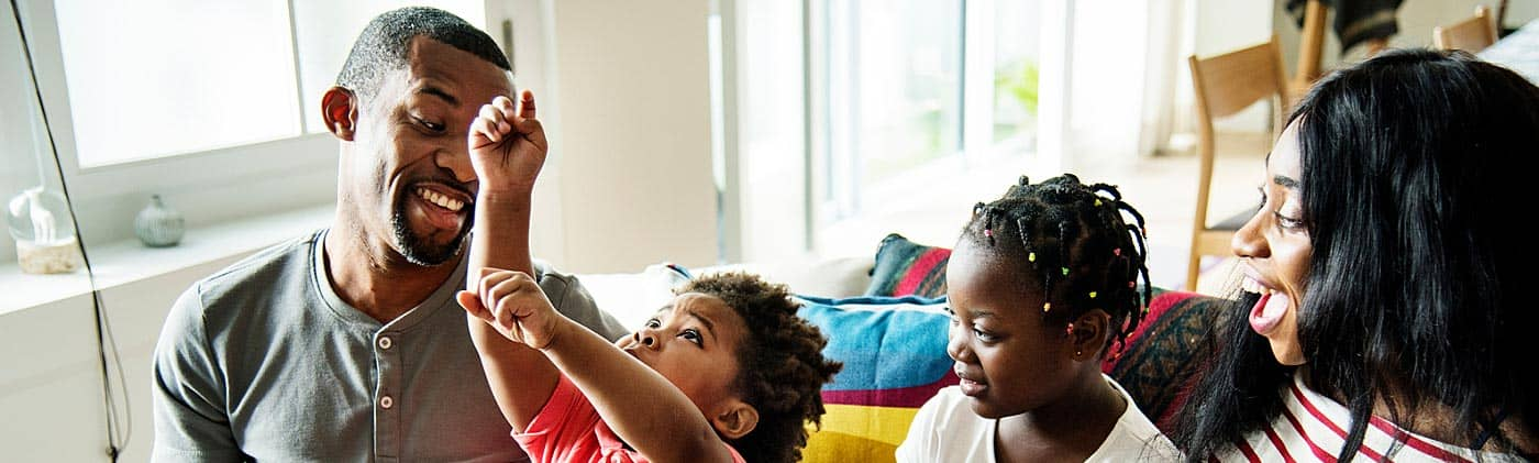 parents play with their kids on the couch and discuss what it means to buy term and invest the difference