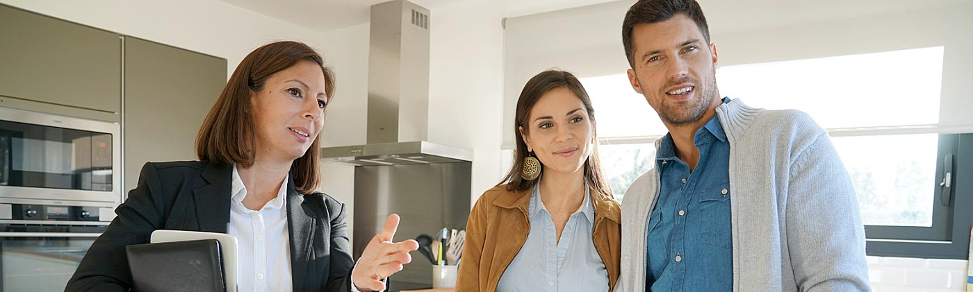 real estate agent shows a house to a young couple after they hire her to help them with buying a home