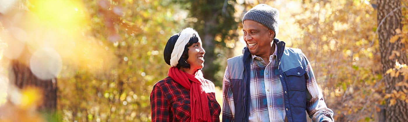 retired couple walk through autumn woods to discuss questions about choosing an immediate annuity