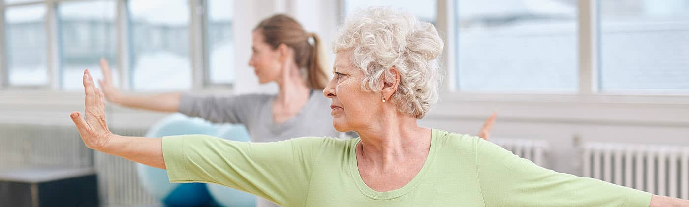 Retired woman teaching a yoga class after looking at cool retirement jobs
