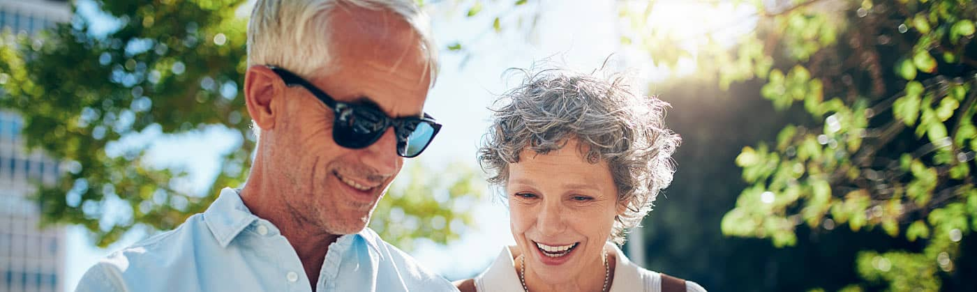 Senior couple checking map on a walk and talking about starting an emergency fund in retirement