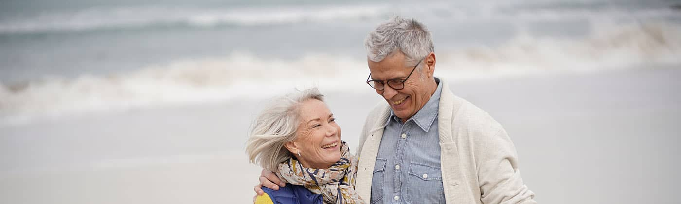Senior couple enjoying a walk on the beach and discussing a possible lost 401(k)