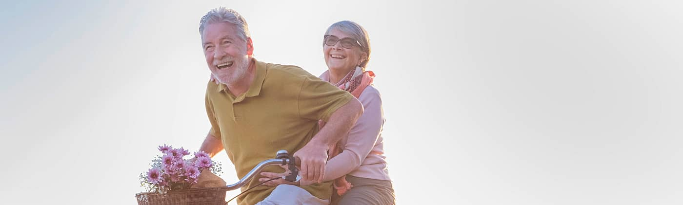 Senior couple riding a bike on a sunny day