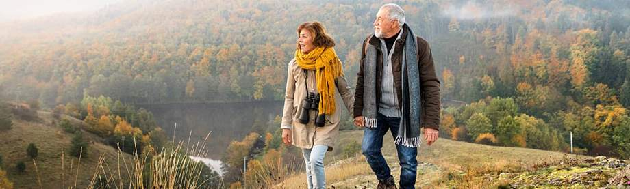 Senior couple takes a walk outdoors and discusses if they should purchase life insurance