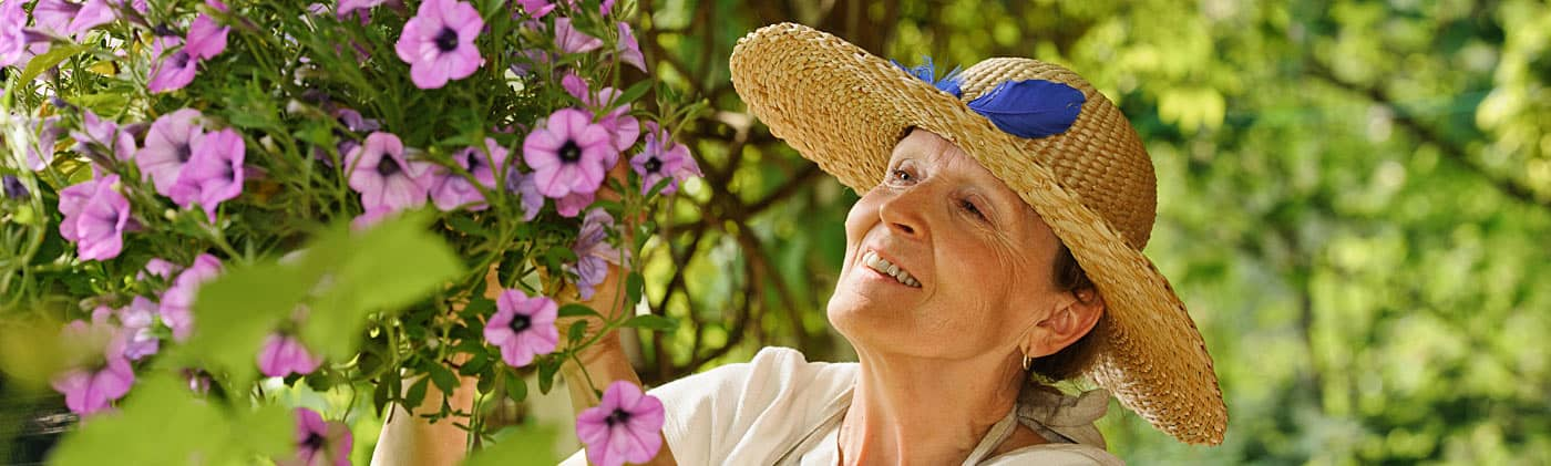 Senior woman smelling flowers on a tree while thinking about retirement catch-up contributions