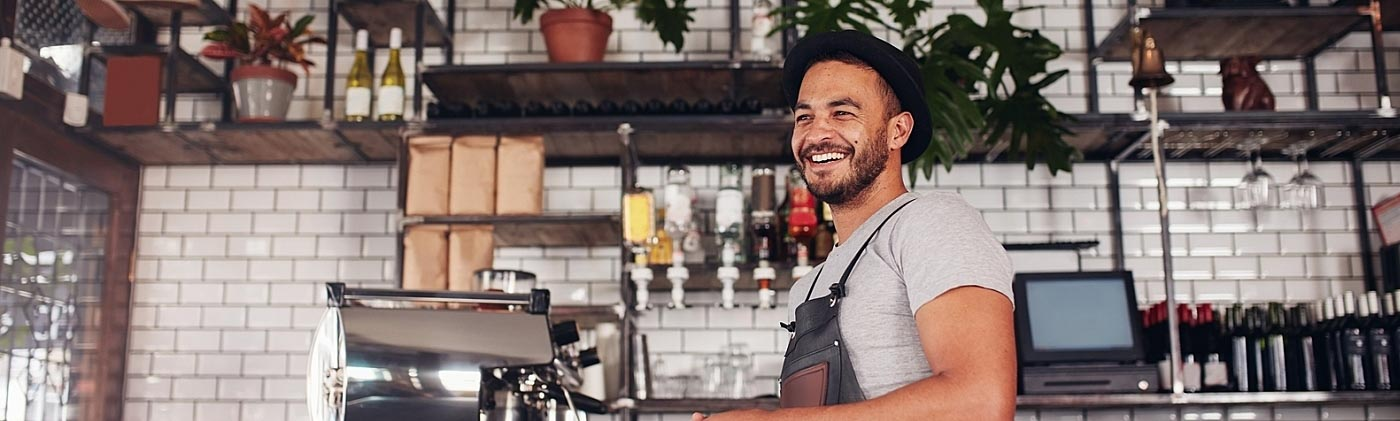 male coffee shop owner smiles inside his cafe and plans to build a quality employee benefits package