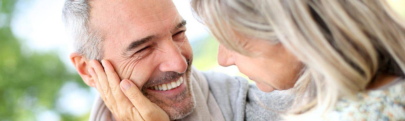 smiling senior couple, happy to have medicare supplement insurance, embraces each other outside