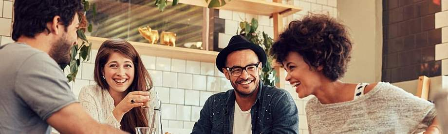 two 30-something couples drink coffee at a table in a café and discuss budgeting tips together