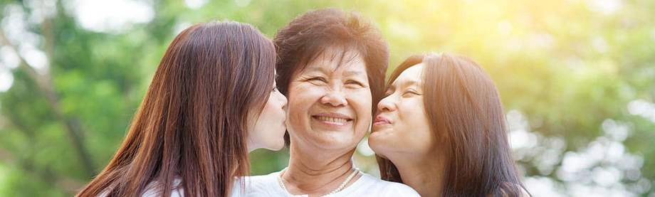 two daughters kiss their mom on the cheek as they discuss buying life insurance to protect the family