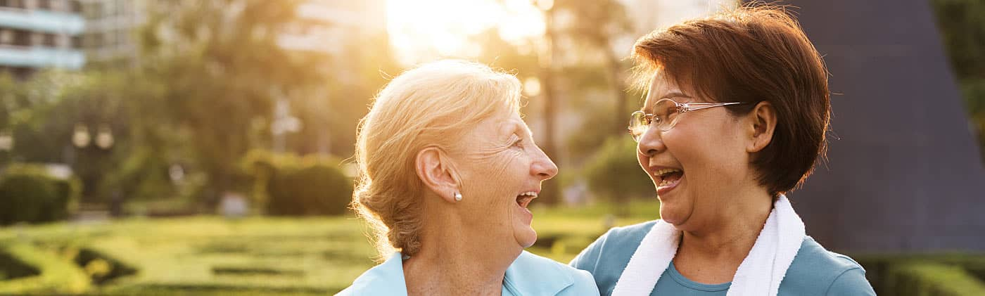 Two elderly women looking at each other smiling and talking about age-related cognitive decline