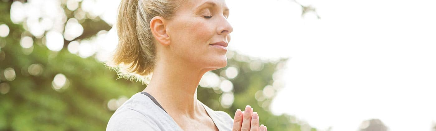 woman practices meditative yoga pose outside as stress reduction to improve her long-term health