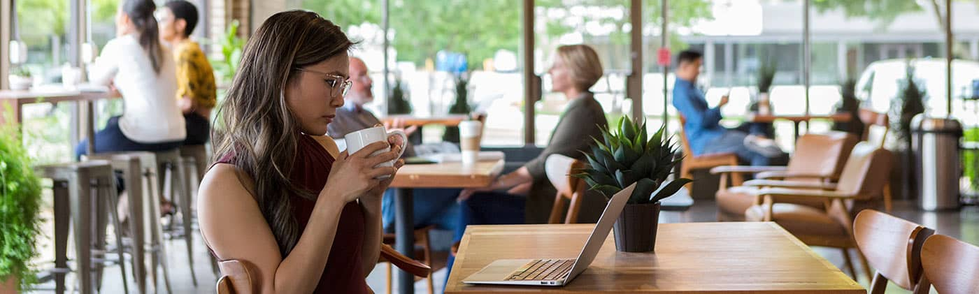 Woman freelancer working on laptop while sitting at the window in a coffee shop: irregular income