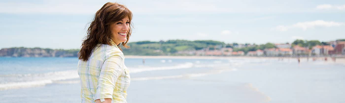 Woman walking on a beach and wondering how to improve your finances