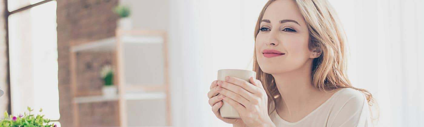 young female professional sips coffees at her desk and makes plans for an early retirement