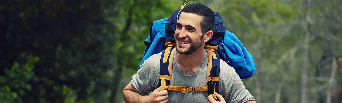 Young, happy hiker carrying a backpack up a hill and wondering if single people need life insurance