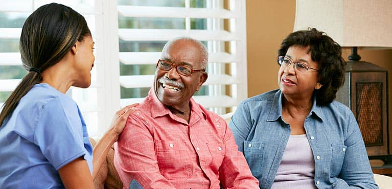 A caregiver speaks with a mature couple in their home: assisted living costs