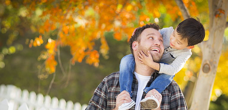 A father carries his young son on his shoulders outdoors in the fall: estate plan