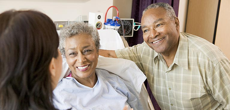A hospital doctor speaks with a mature couple: living benefits