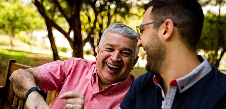 a mature father and his middle-aged son laugh together in a park fixed indexed annuity