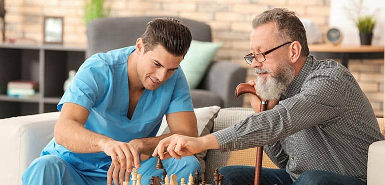 A mature man plays a game of chess with his caregiver costs of long-term care