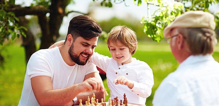 A retired man plays chess in the park with his son and young grandson: things to do in retirement