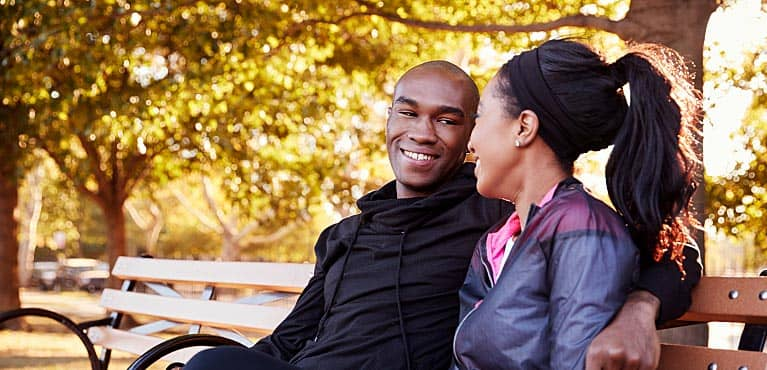 A smiling young couple sits on a bench together in a park: pension plan