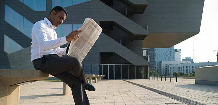 Businessman sitting outside and checking performance of mutual funds vs. stocks in newspaper