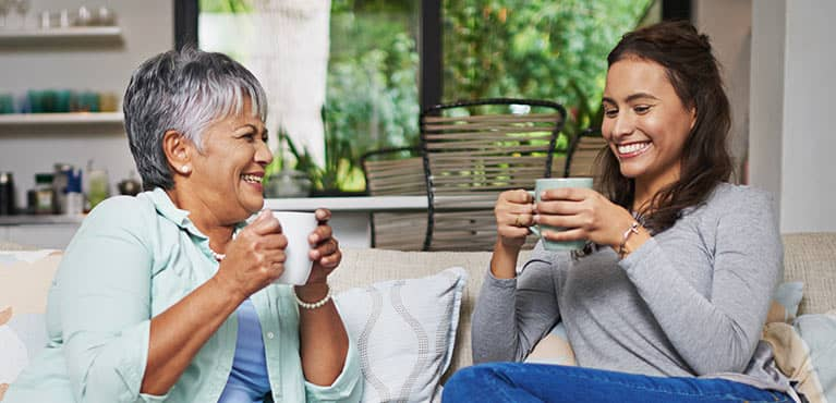 Two ladies enjoying a laugh over a cup of coffee