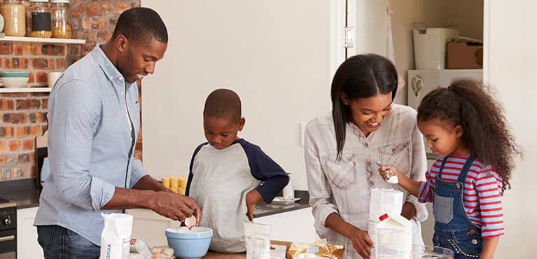 Mom and dad with son and daughter baking in the kitchen