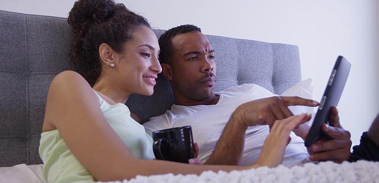Couple in bed safe from cybersecurity and identity theft thanks to good internet practices